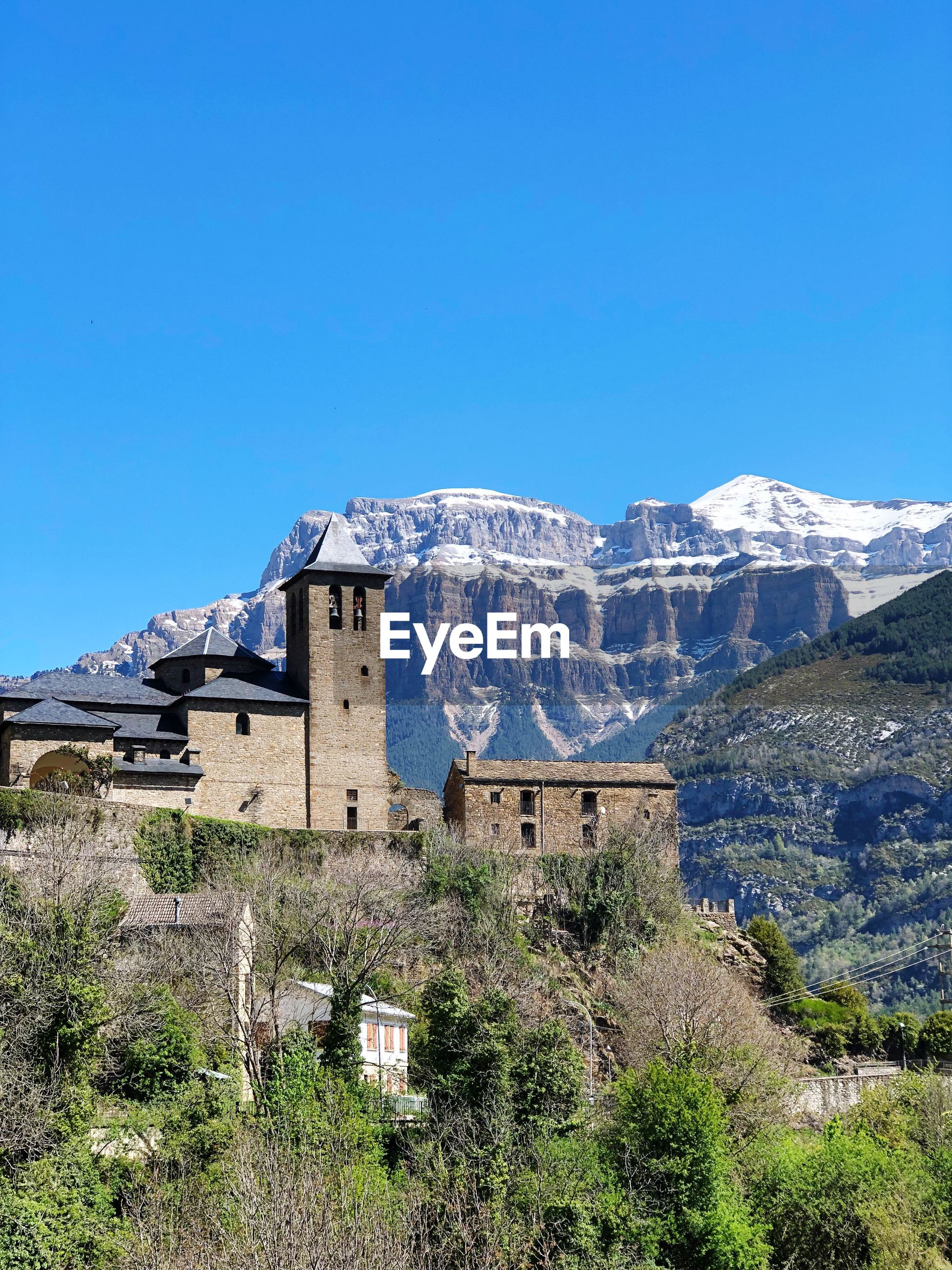 BUILDINGS AGAINST CLEAR BLUE SKY WITH MOUNTAIN RANGE IN FOREGROUND