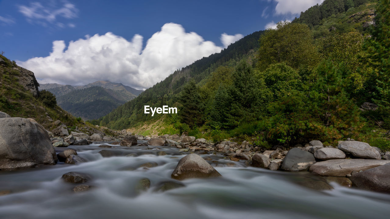 Scenic view of river amidst rocks against sky