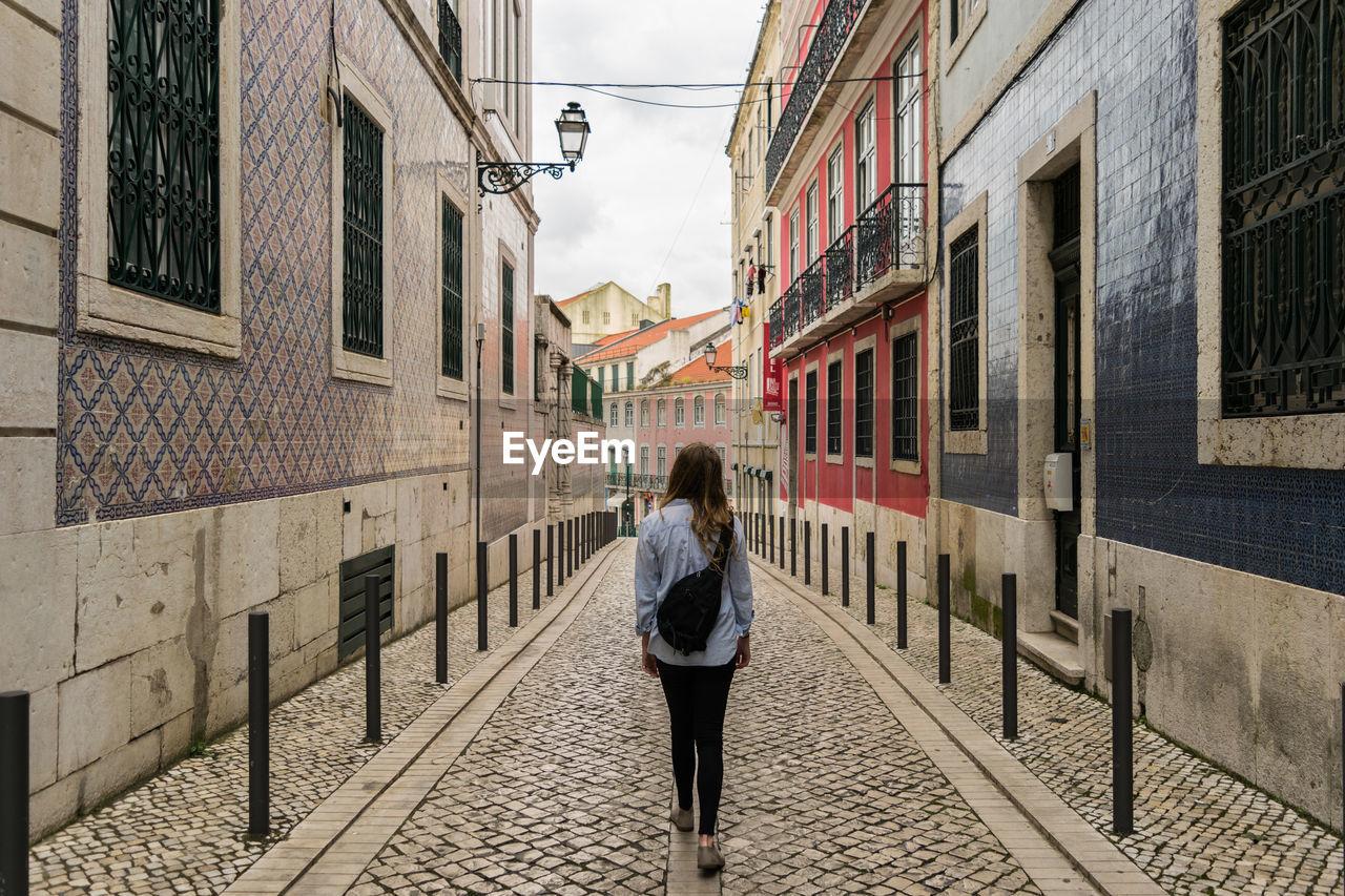 Woman Walking On Narrow Alley Amidst Buildings