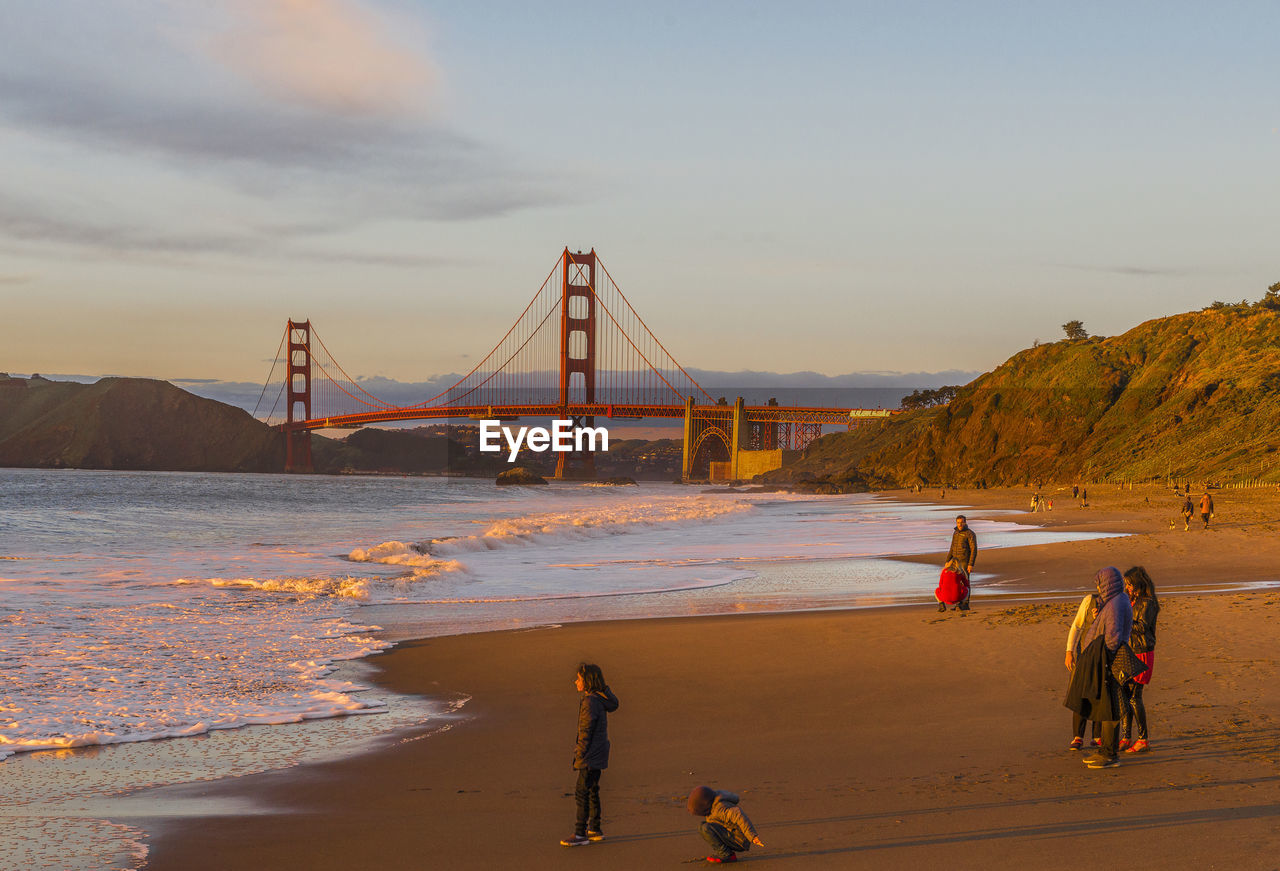 sky, water, bridge, suspension bridge, bridge - man made structure, transportation, connection, nature, travel destinations, real people, group of people, tourism, built structure, sea, architecture, men, travel, land, engineering, bay, outdoors