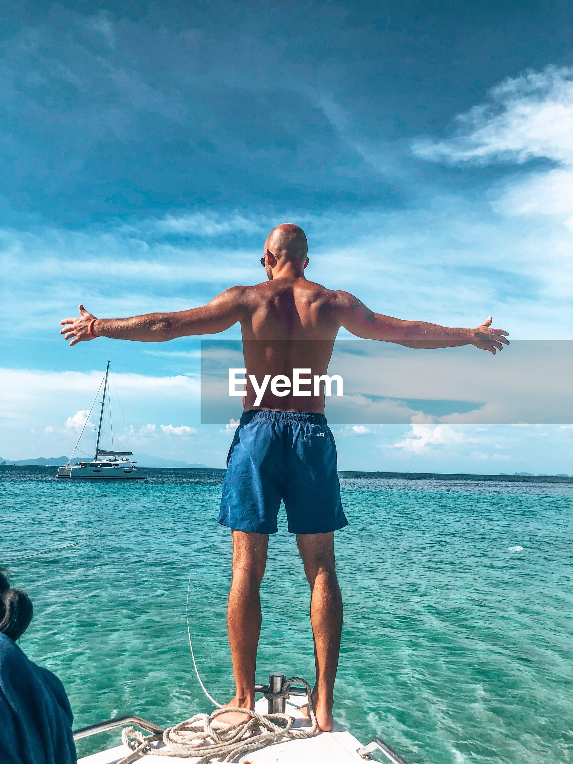 Full length rear view of shirtless man with arms outstretched standing on sailboat in sea against sky