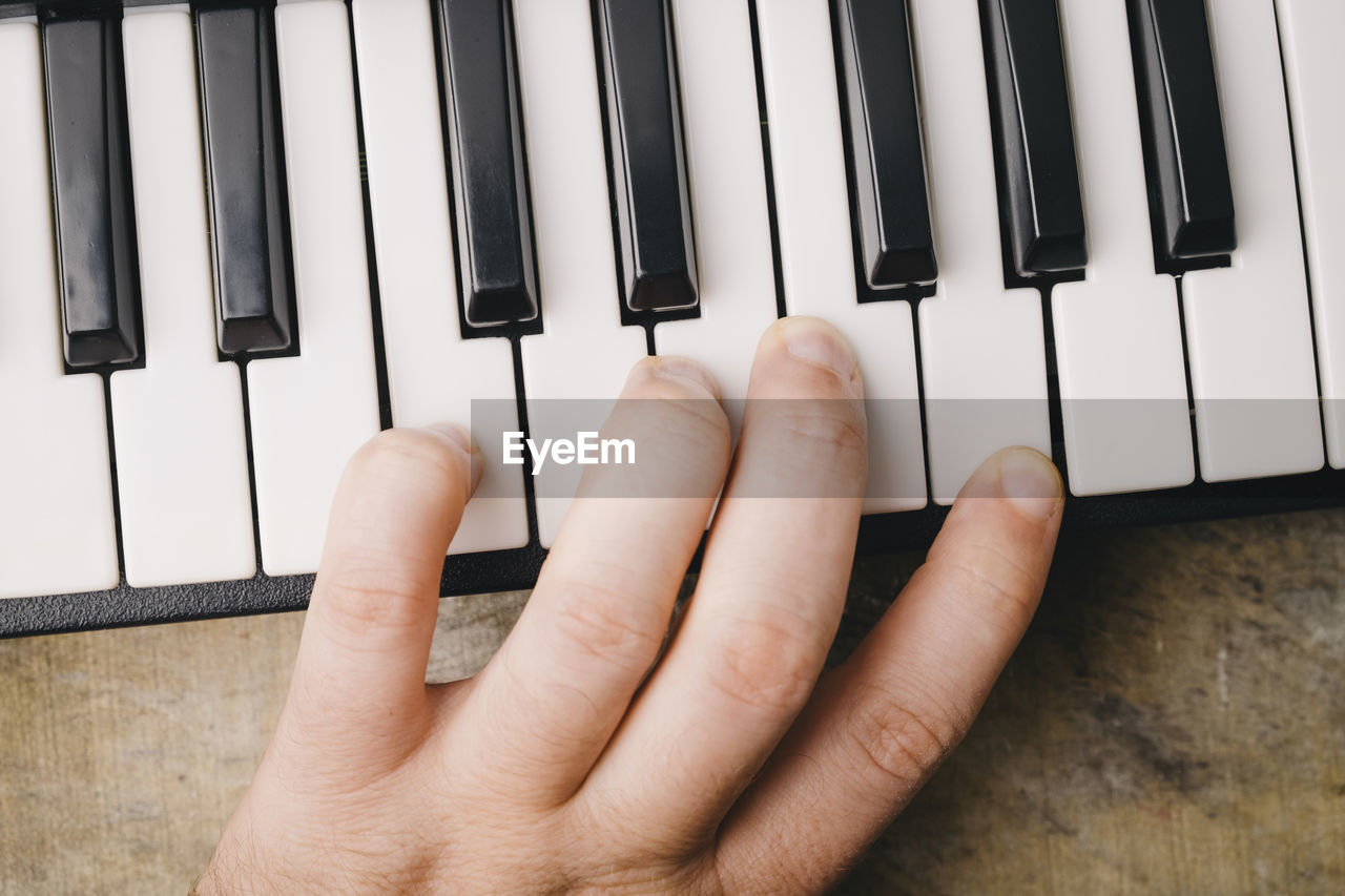 Cropped Hand Of Person Playing Piano