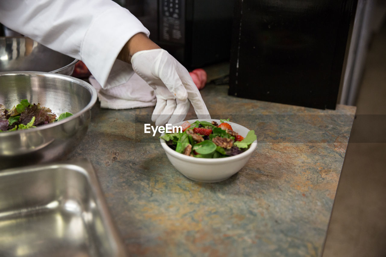 Cropped Hand Of Chef By Food Bowl In Kitchen At Restaurant