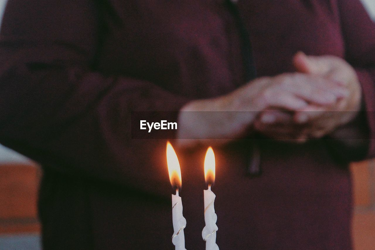 Midsection Of Person Standing By Candles