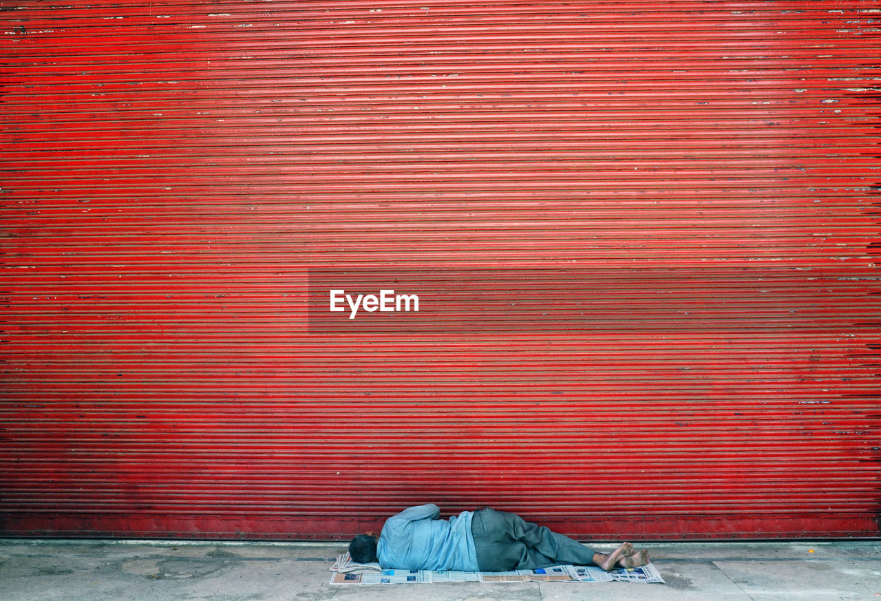 Rear View Of Homeless Man Sleeping On Footpath By Closed Red Shutter
