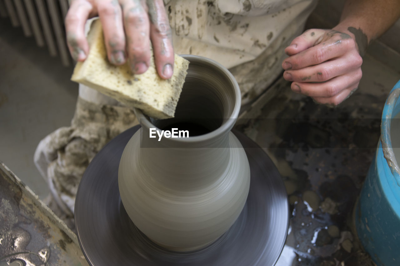 Midsection Of Man Making Earthenware In Workshop