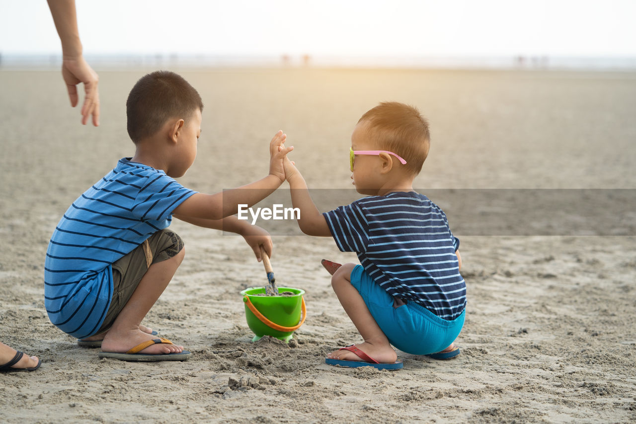 childhood, child, boys, males, real people, men, beach, togetherness, two people, land, leisure activity, lifestyles, casual clothing, full length, water, sand, bonding, preschool age, innocence, cute, outdoors