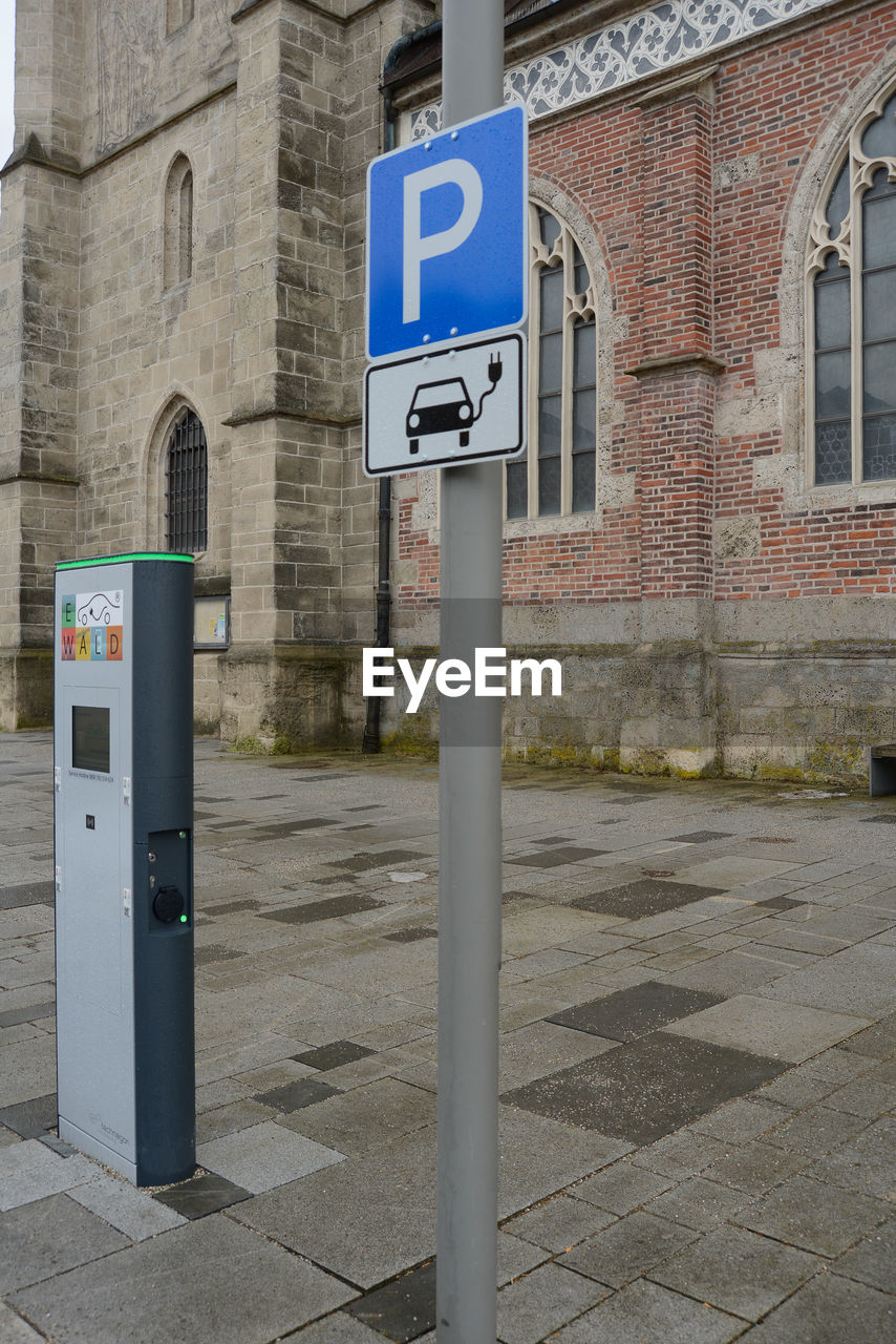 communication, number, parking sign, building exterior, built structure, architecture, day, outdoors, no people, road sign, pay phone, city, wheelchair access