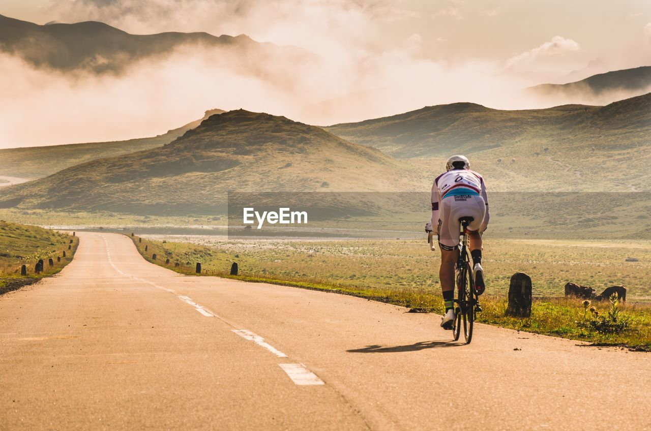 transportation, road, sky, bicycle, land vehicle, mountain, mode of transportation, lifestyles, real people, cloud - sky, nature, direction, one person, the way forward, riding, sport, helmet, activity, beauty in nature, outdoors