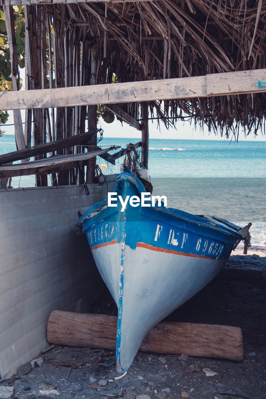 water, nautical vessel, no people, day, wood - material, transportation, moored, blue, nature, mode of transportation, beach, outdoors, land, sea, tranquility, wood, pier, tree, beauty in nature, rowboat