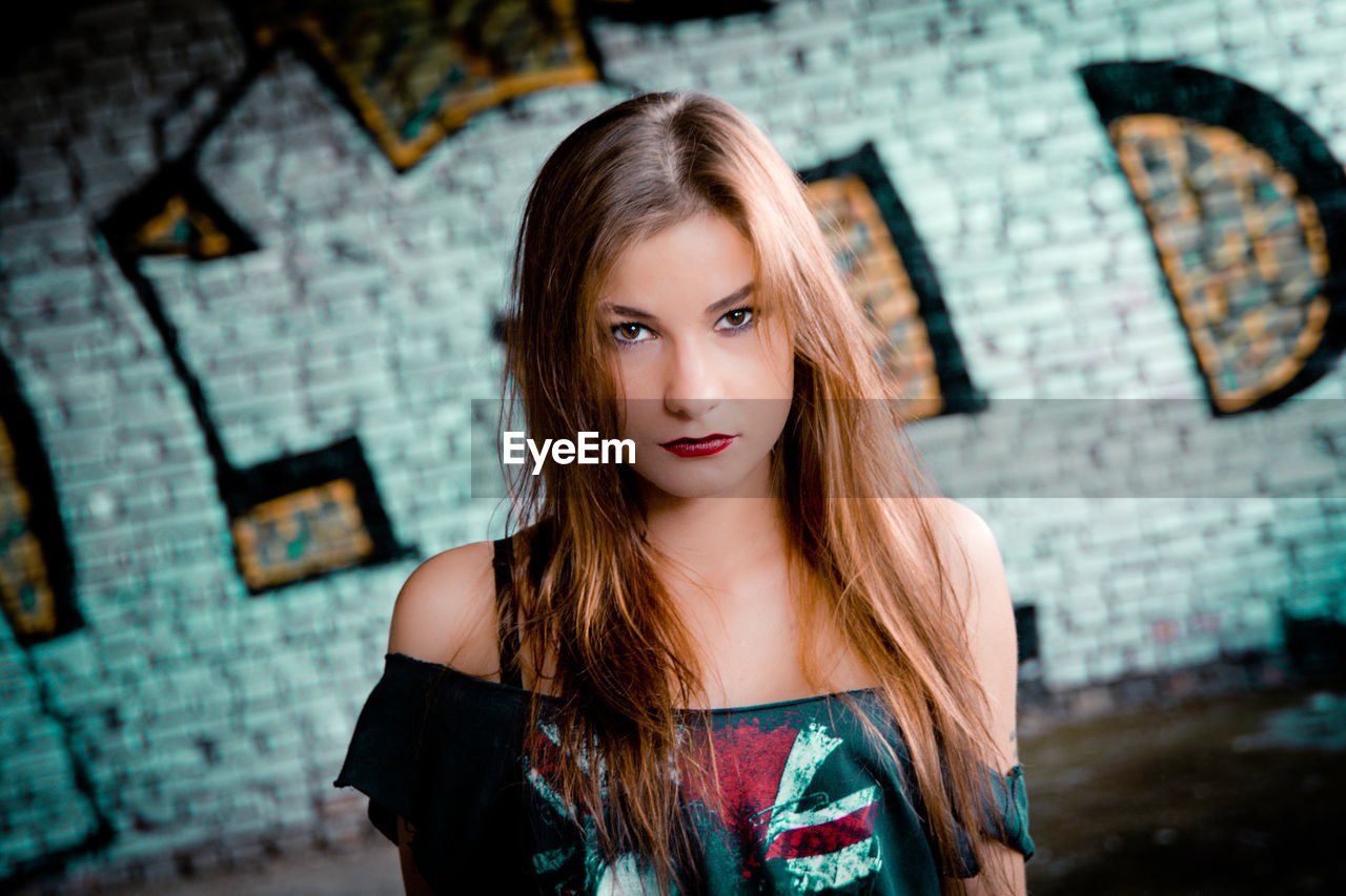 Portrait of young woman against graffiti wall on street