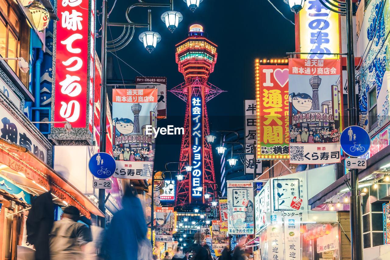 Illuminated street shinsekai hitachi building at osaka city at night