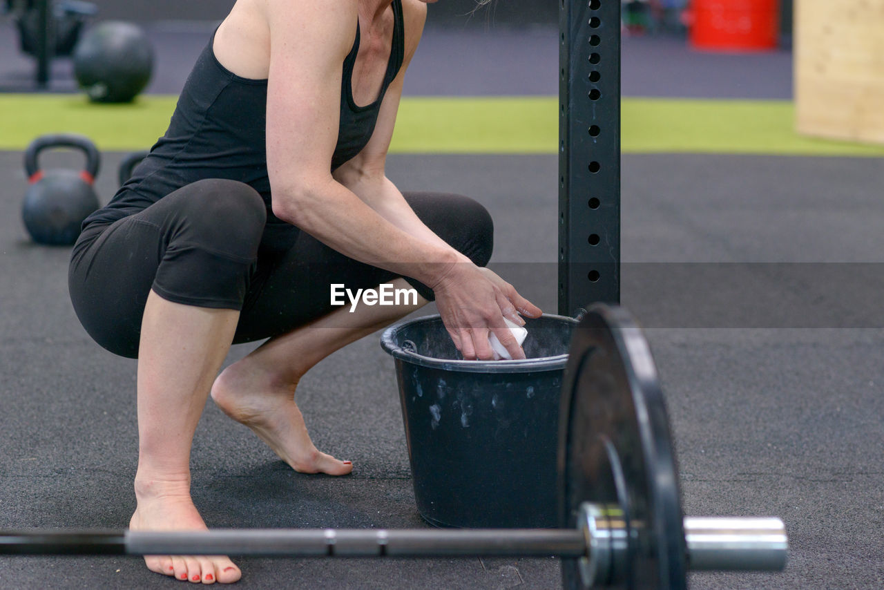 Low section of female athlete applying sports chalk while crouching in gym