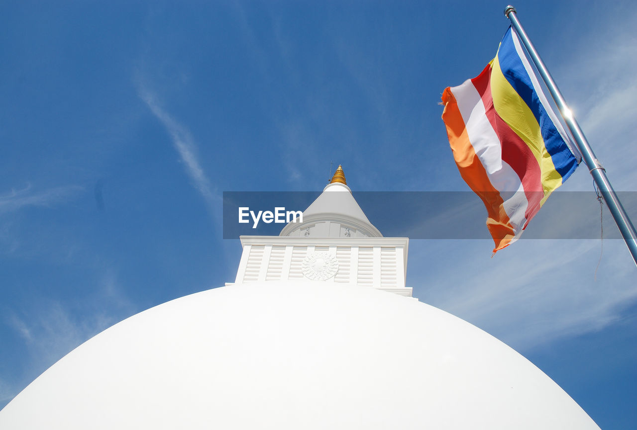 sky, cloud - sky, built structure, low angle view, building exterior, architecture, flag, religion, belief, no people, nature, spirituality, day, patriotism, place of worship, white color, blue, building, sunlight, wind, outdoors, spire