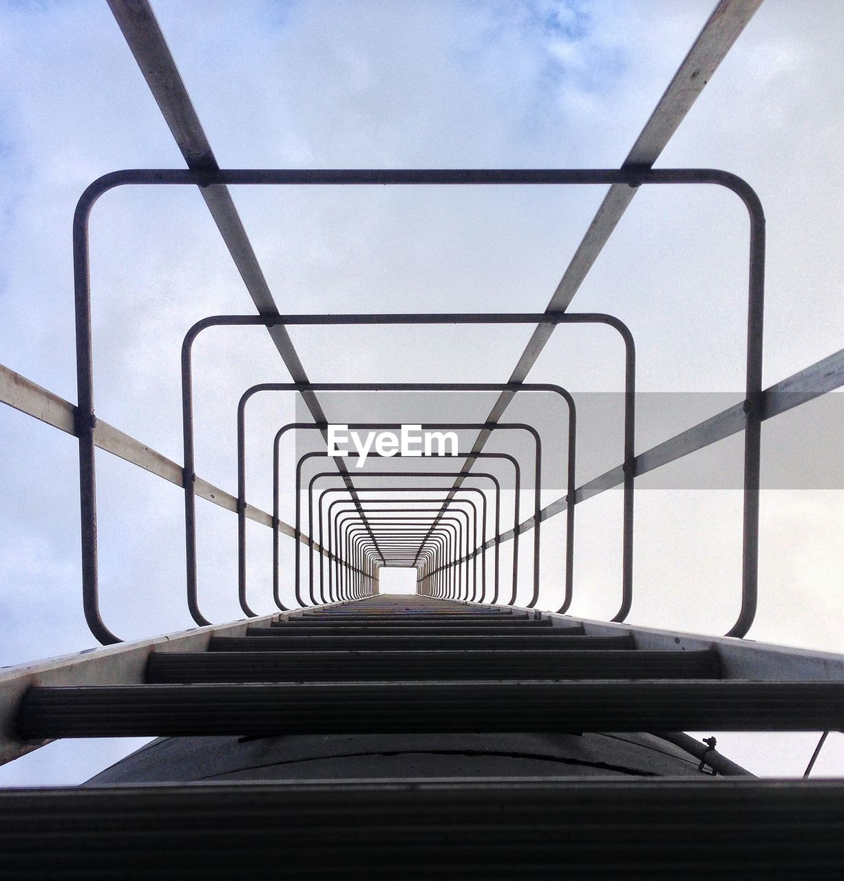 Low Angle View Of Ladder Against Cloudy Sky