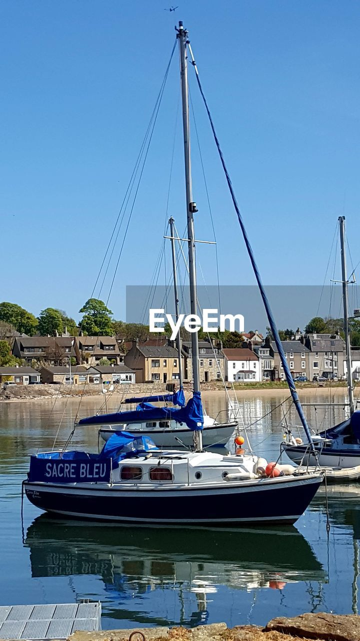 nautical vessel, moored, water, mode of transport, transportation, boat, mast, waterfront, sailboat, blue, outdoors, architecture, no people, built structure, day, building exterior, nature, harbor, yacht, sea, clear sky, sky