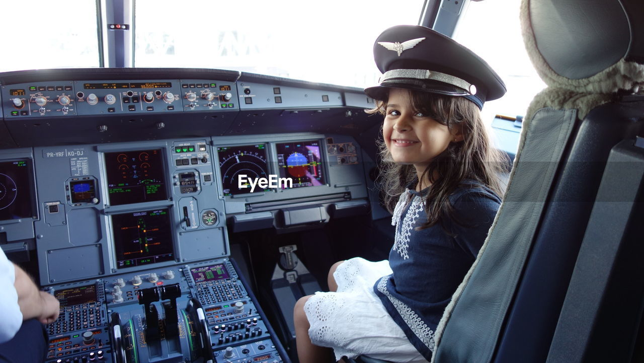Portrait of smiling girl wearing pilot cap sitting in airplane cockpit