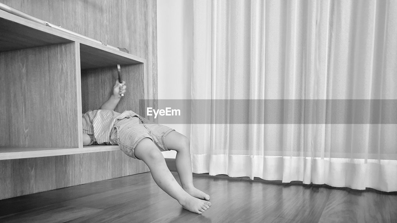 Low section of boy lying in shelf