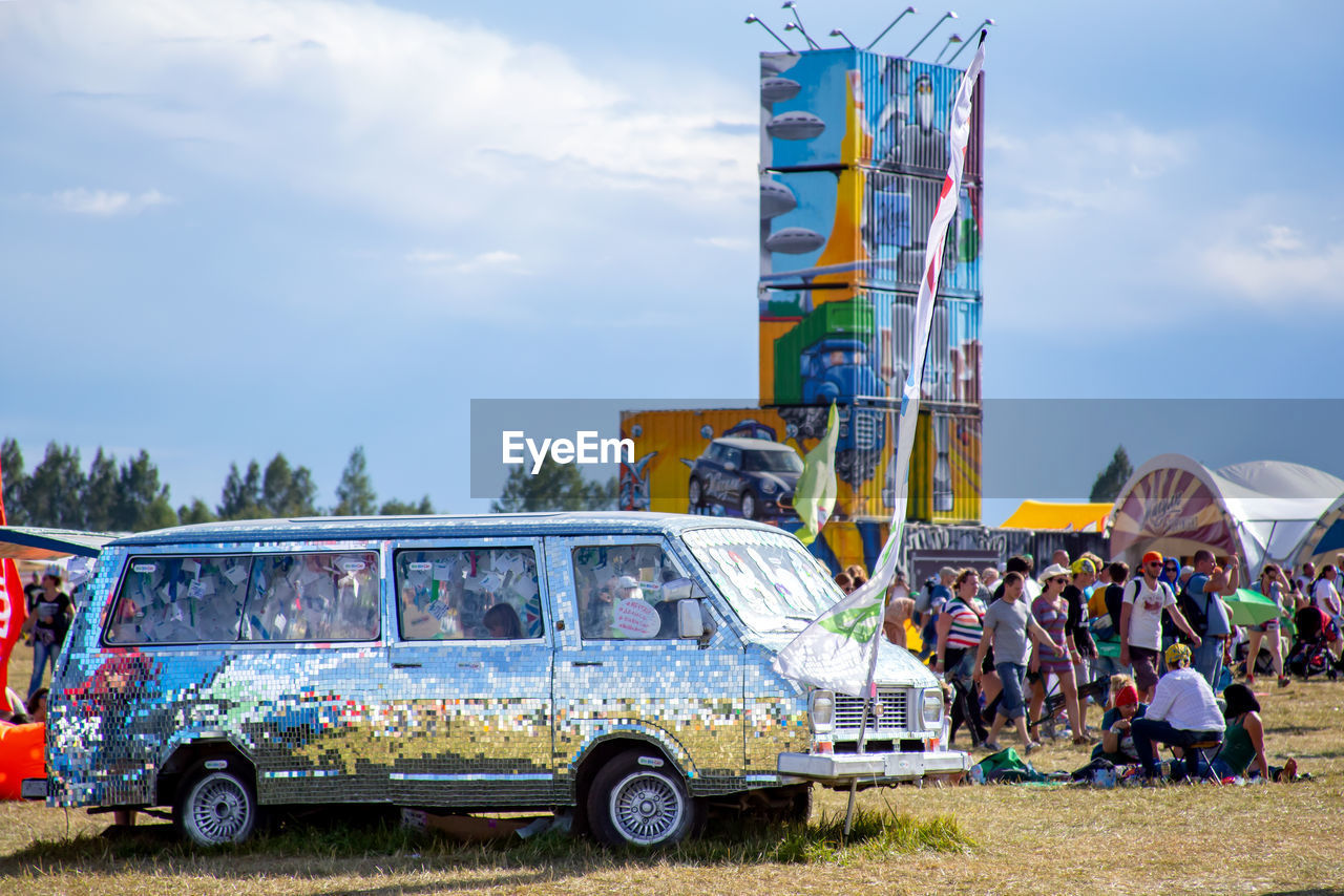 transportation, mode of transportation, sky, cloud - sky, real people, day, land vehicle, group of people, nature, men, outdoors, architecture, adult, travel, car, people, motor vehicle, public transportation, building exterior, arts culture and entertainment