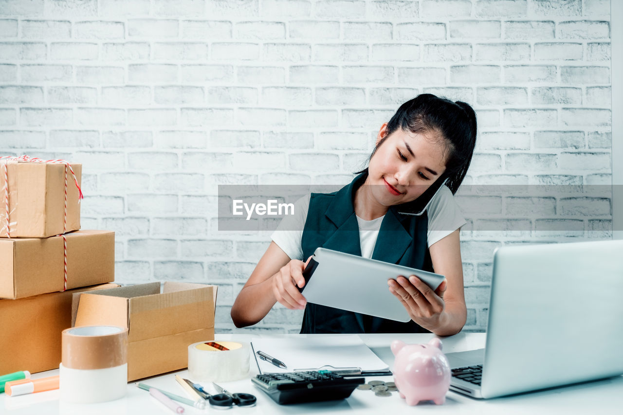 wireless technology, business person, one person, adult, women, business, computer, communication, indoors, table, office, brick wall, technology, occupation, working, laptop, businesswoman, young adult, front view, brick, using laptop