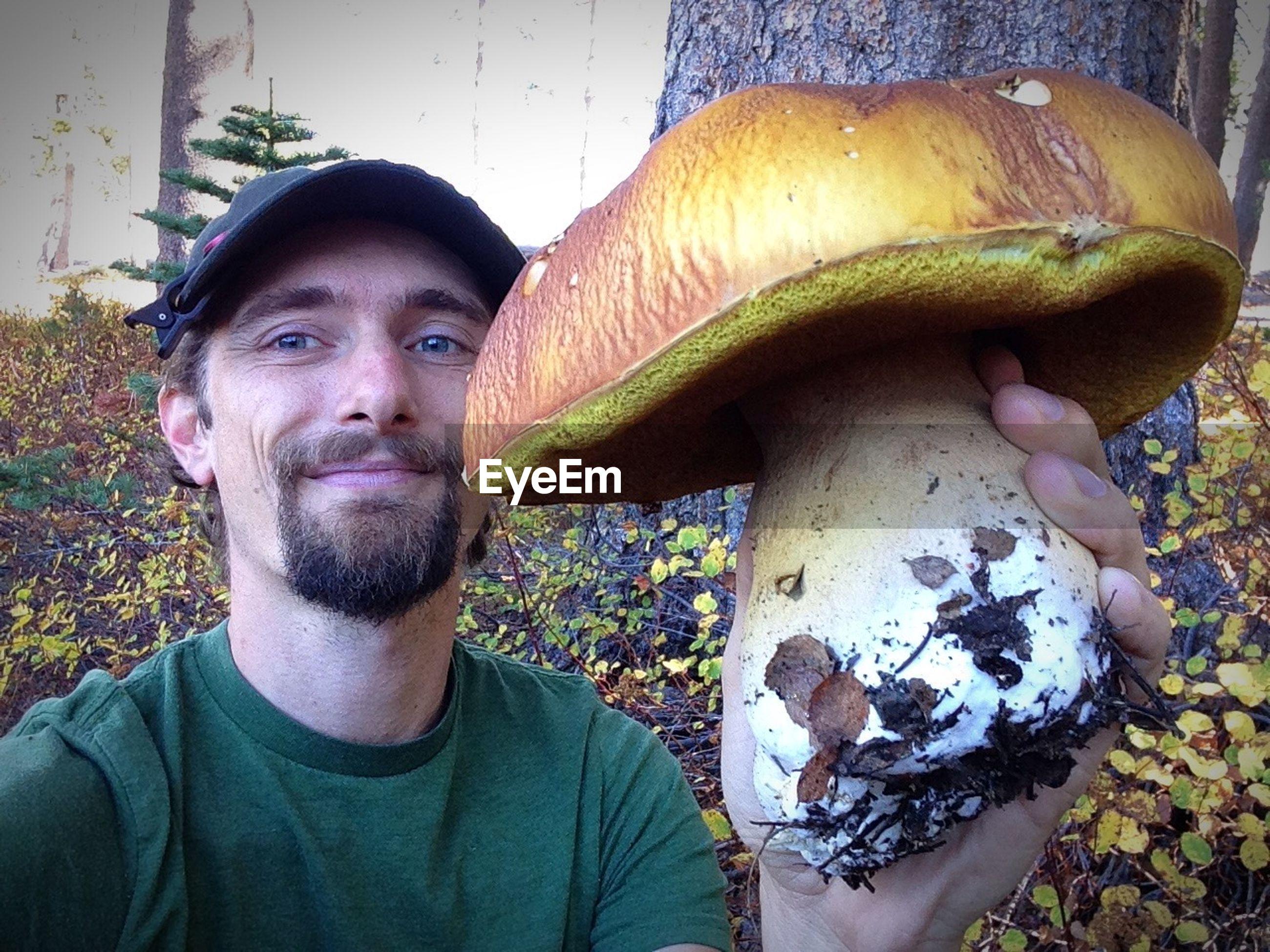 Smiling man holding mushroom in forest