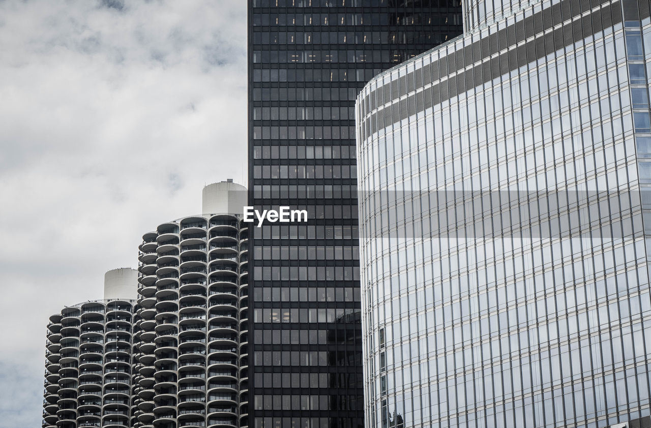 LOW ANGLE VIEW OF OFFICE BUILDING AGAINST CLOUDY SKY