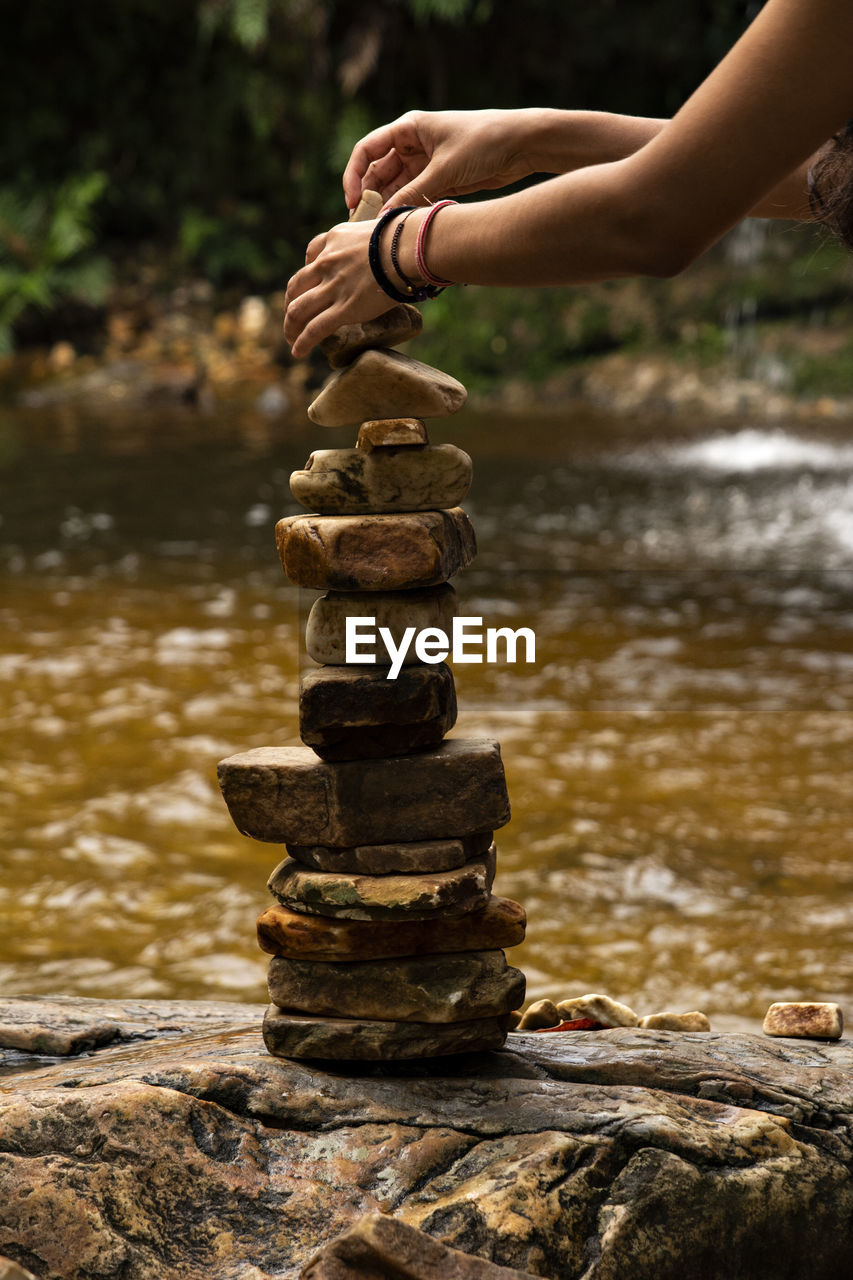 human hand, human body part, water, hand, rock, solid, stone - object, focus on foreground, stack, one person, balance, body part, nature, rock - object, day, human finger, real people, finger, unrecognizable person, outdoors, pebble, human limb, flowing water