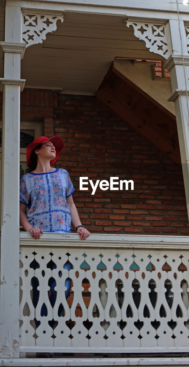 Low angle view of woman looking away while standing on balcony