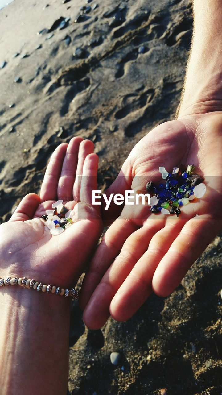 human body part, human hand, hand, body part, real people, people, day, leisure activity, holding, close-up, nature, lifestyles, rock, human finger, finger, two people, solid, personal perspective, outdoors, land