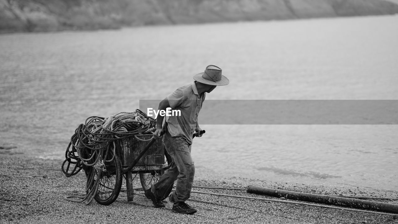 Man Pulling Cart With Ropes At Beach