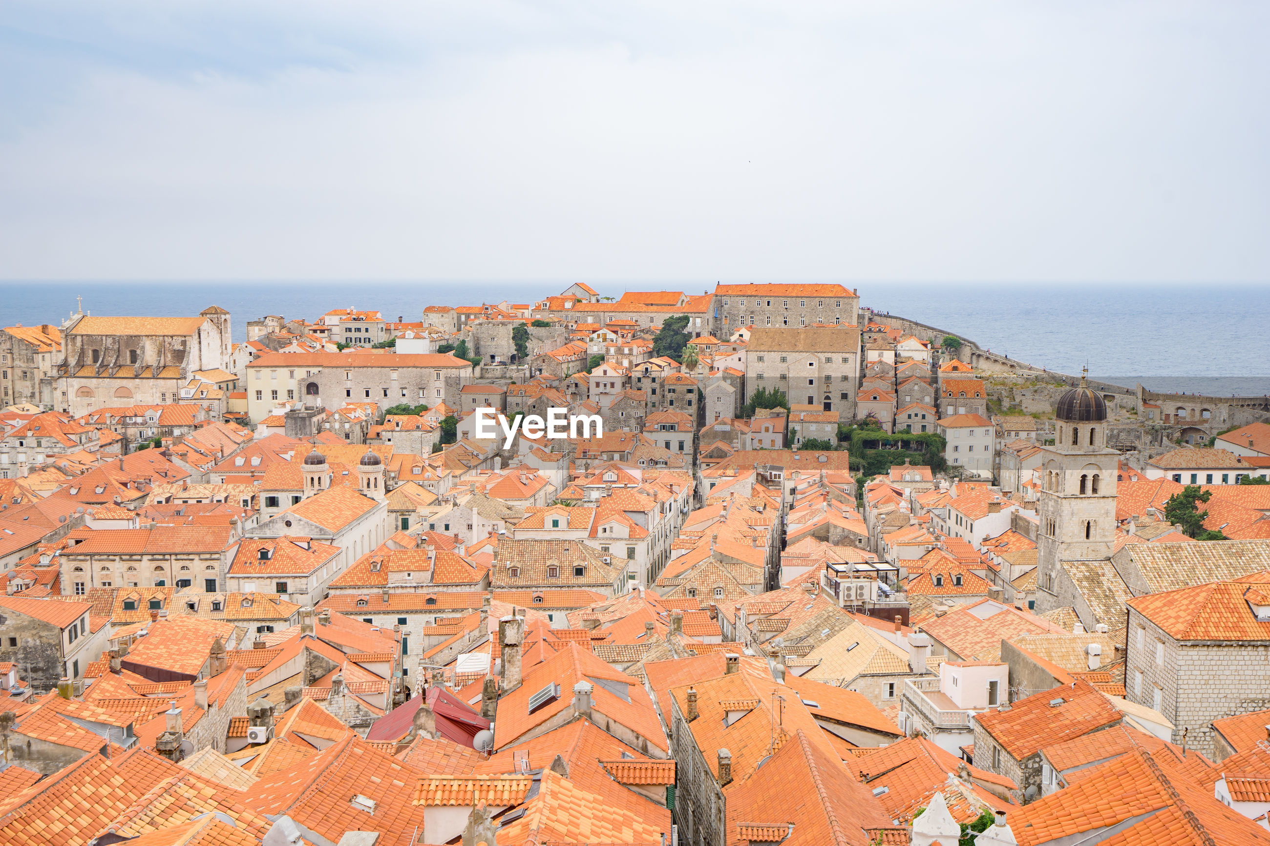 HIGH ANGLE VIEW OF TOWNSCAPE BY SEA AGAINST SKY IN TOWN