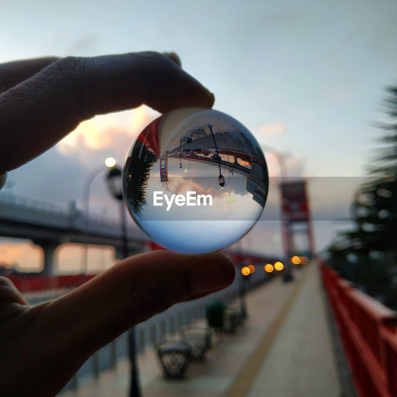 human hand, hand, human body part, sphere, holding, building exterior, city, one person, real people, personal perspective, architecture, crystal ball, close-up, focus on foreground, street, built structure, day, finger, glass - material, reflection, body part, outdoors