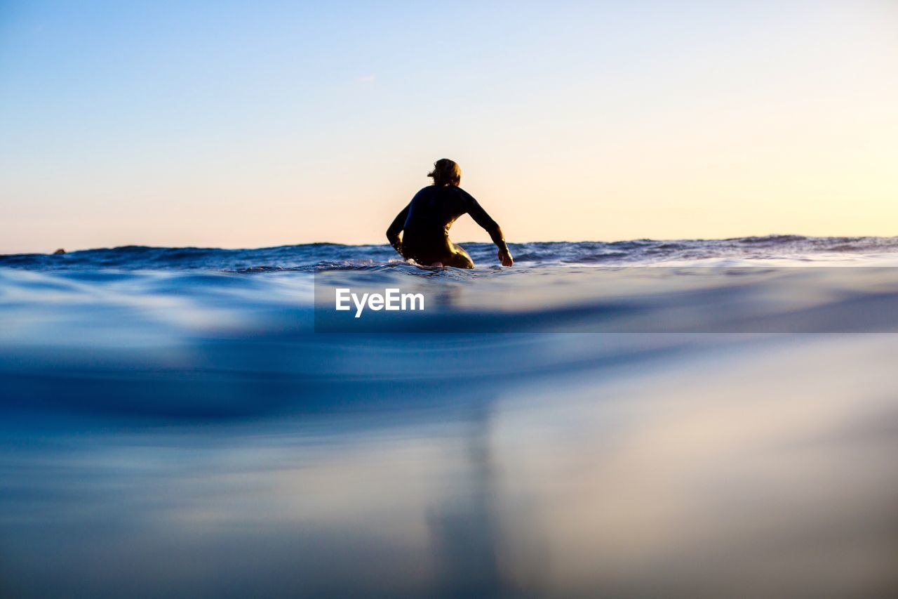 Man surfing on sea against clear sky