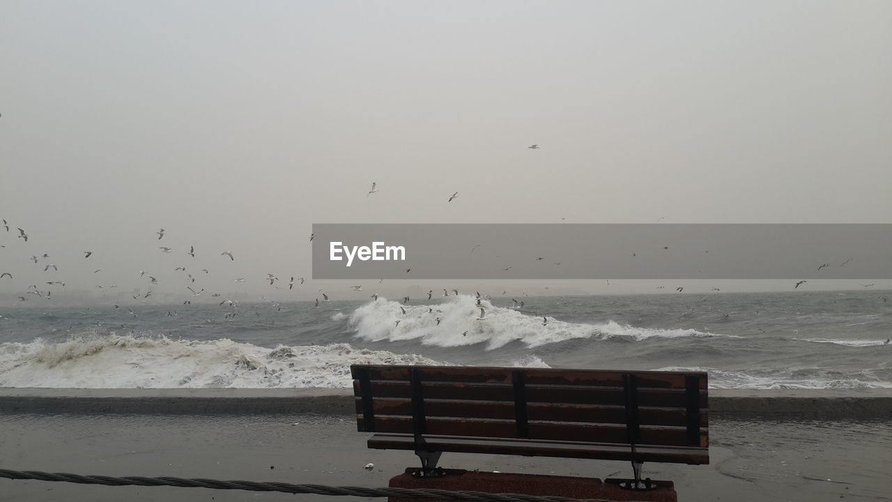 Bench On Shore Against Sky