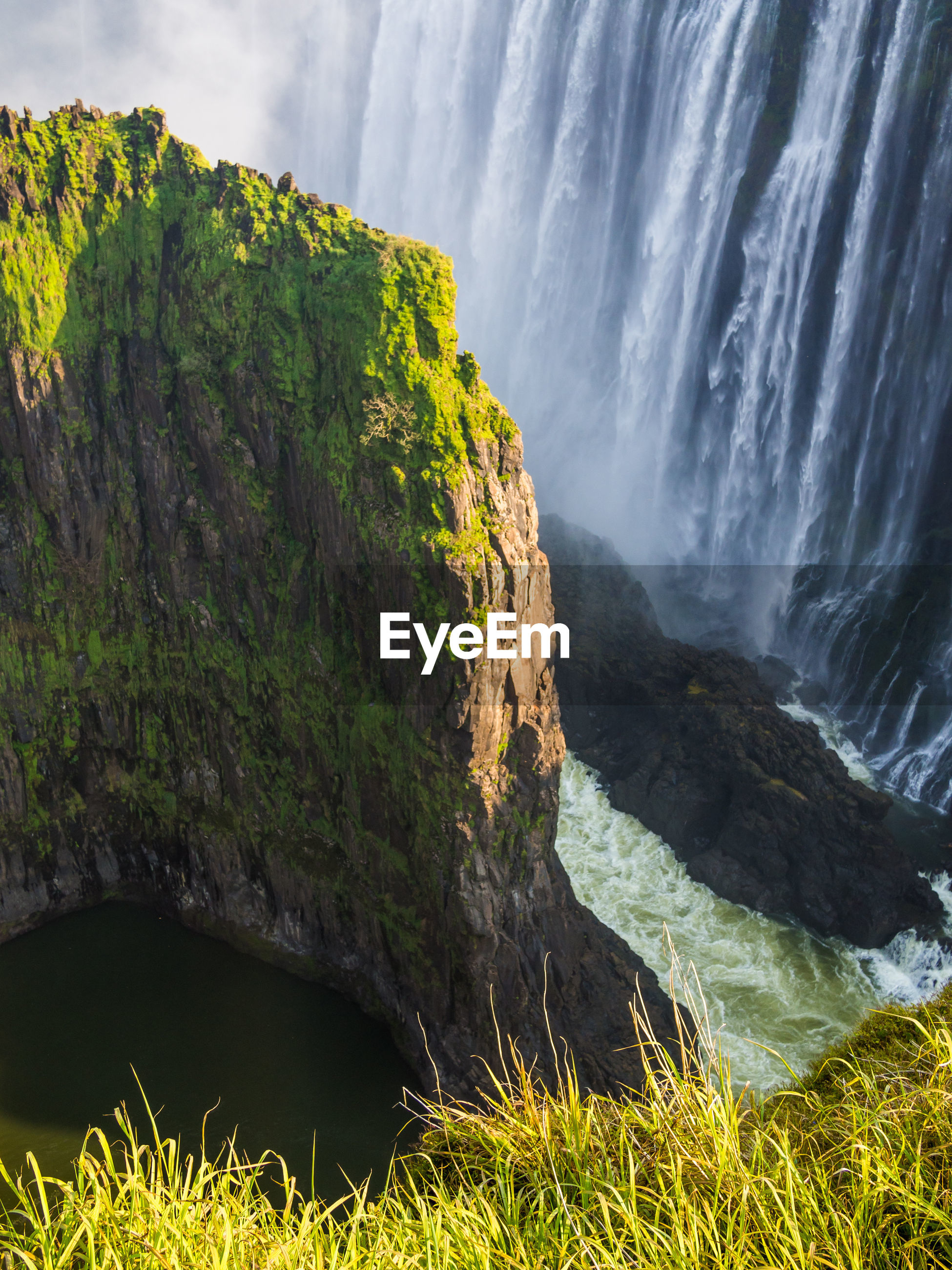 Scenic view of victoria falls waterfall with overgrown cliff and green grass, zambia