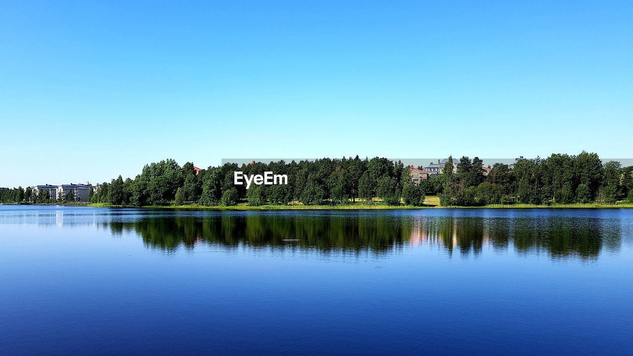 tree, water, plant, sky, reflection, copy space, waterfront, scenics - nature, tranquility, lake, tranquil scene, beauty in nature, clear sky, nature, blue, no people, day, green color, idyllic, outdoors