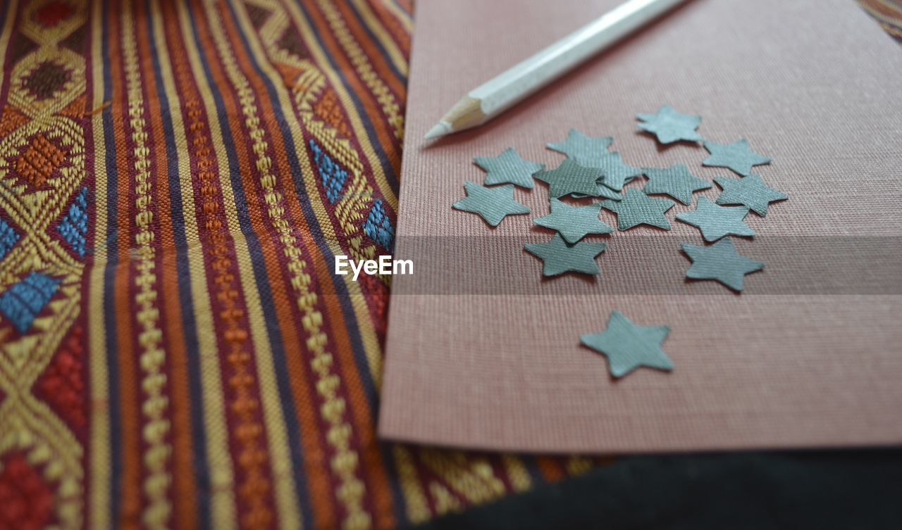 Close-Up Of Star Shape Craft Product By Pencil On Bed