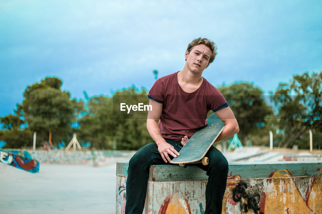 one person, young adult, casual clothing, young men, front view, leisure activity, sitting, three quarter length, day, real people, lifestyles, focus on foreground, tree, nature, portrait, looking at camera, sky, outdoors, contemplation