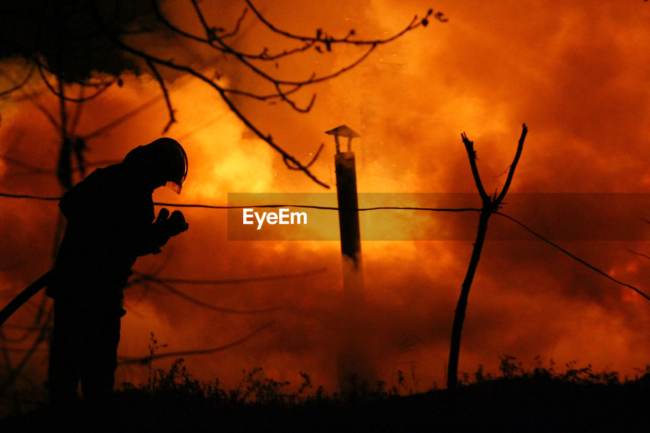 silhouette, orange color, sunset, real people, one person, nature, standing, tree, burning, lifestyles, outdoors, flame, forest fire, men, sky, people, adult