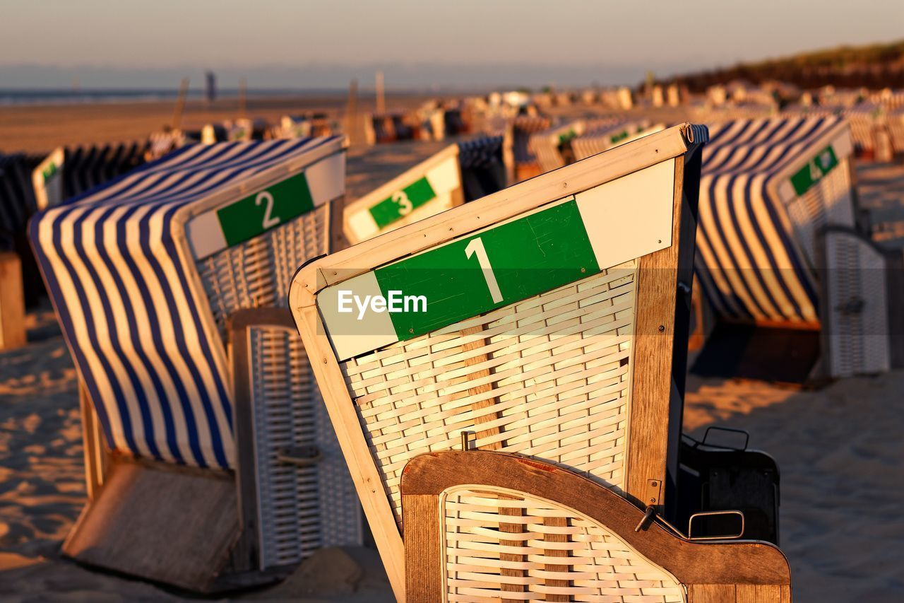 Hooded Beach Chairs At Beach During Sunset