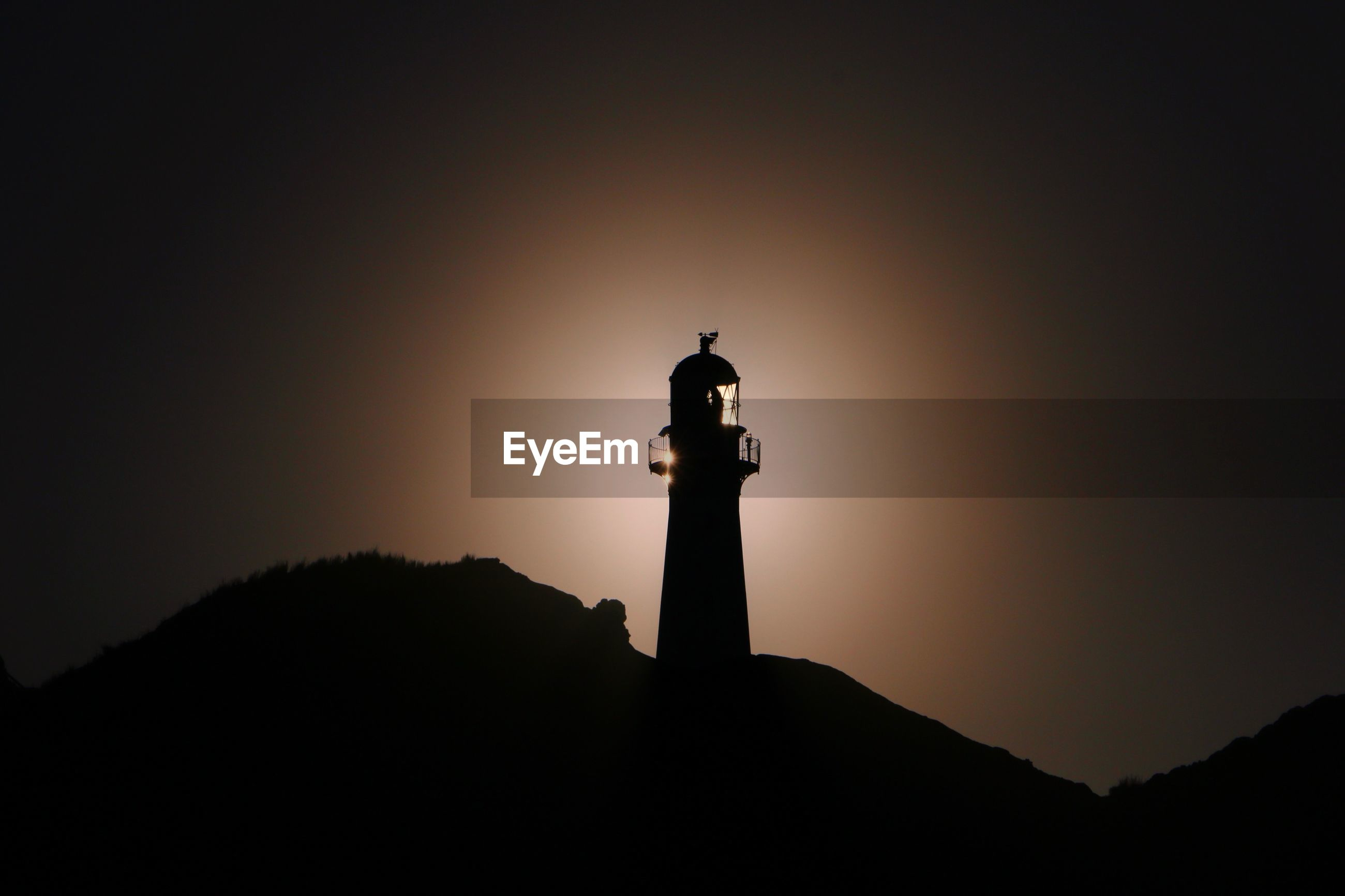 SILHOUETTE OF LIGHTHOUSE BY BUILDING AGAINST SKY DURING SUNSET