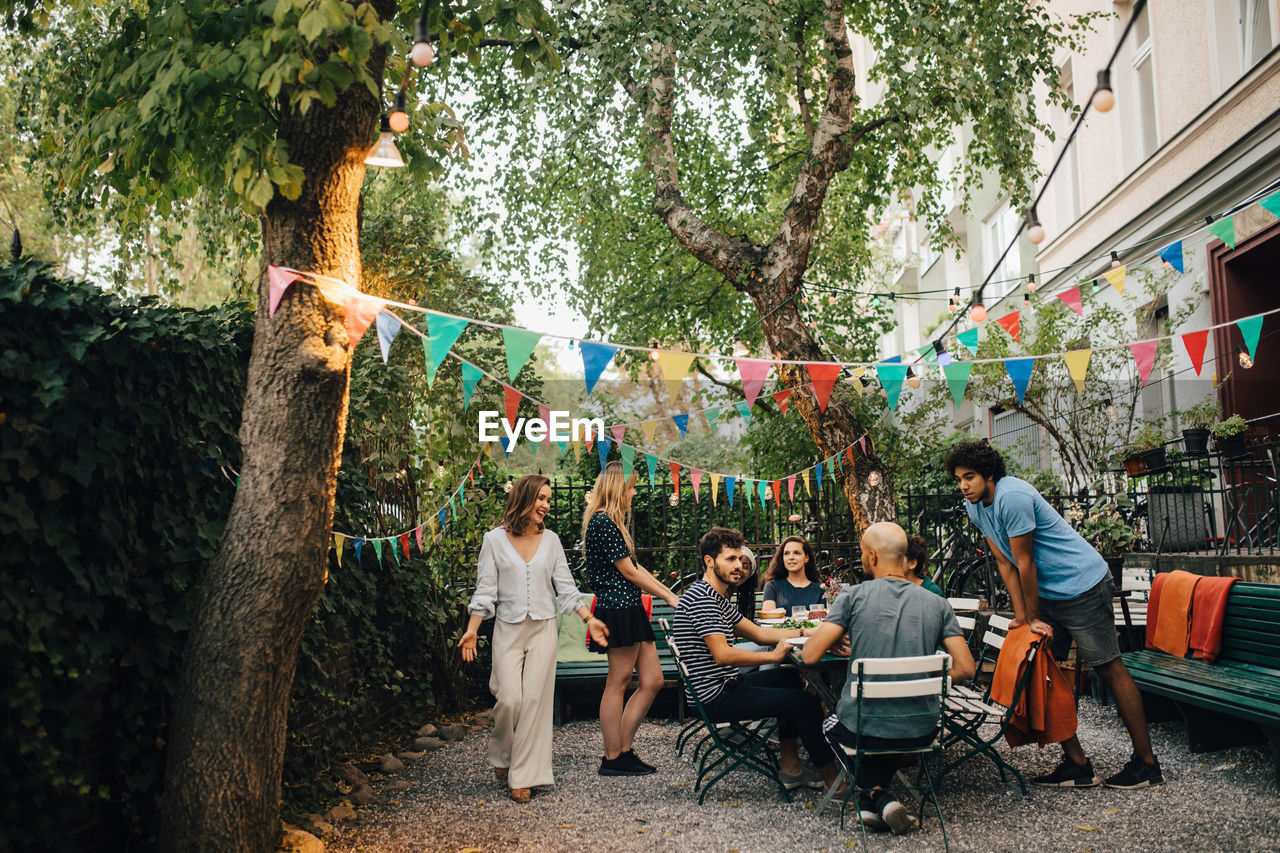 tree, real people, group of people, plant, men, leisure activity, lifestyles, sitting, women, adult, crowd, seat, casual clothing, people, nature, architecture, day, togetherness, table, outdoors