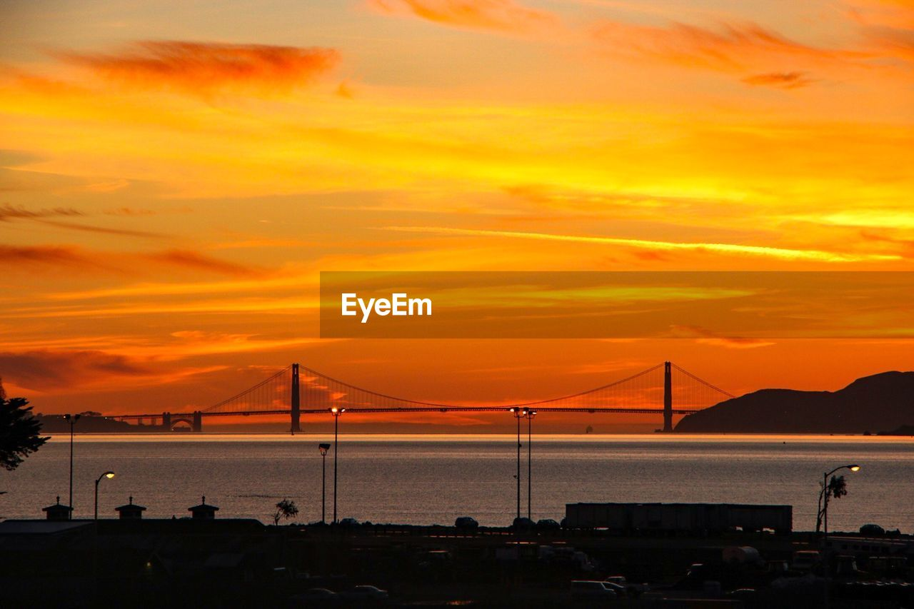sunset, orange color, sky, transportation, dramatic sky, cloud - sky, architecture, water, built structure, connection, sea, beauty in nature, nature, mode of transport, bridge - man made structure, outdoors, silhouette, suspension bridge, scenics, nautical vessel, no people, car, travel destinations, land vehicle, building exterior, mountain, tranquility, beach, city, day