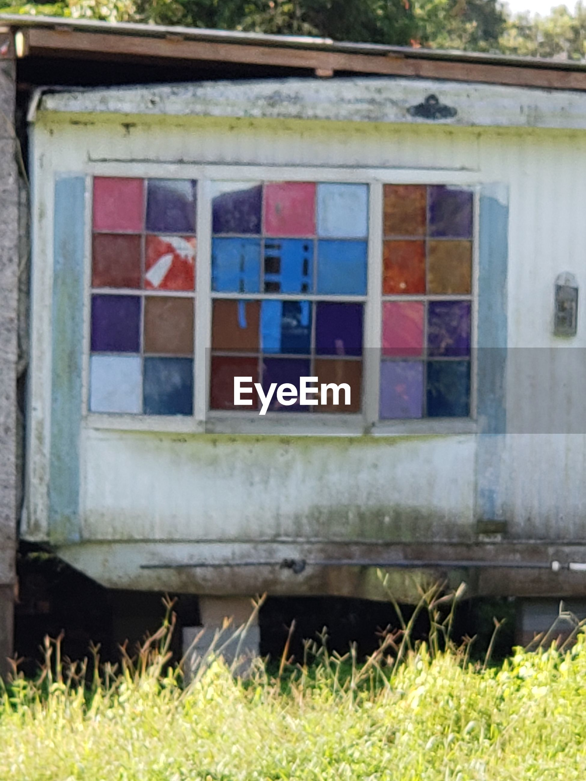 CLOSE-UP OF HOUSE WINDOW ON FIELD AGAINST BUILDING