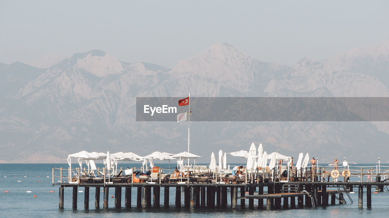 Pier With Sunshade Against Mountains