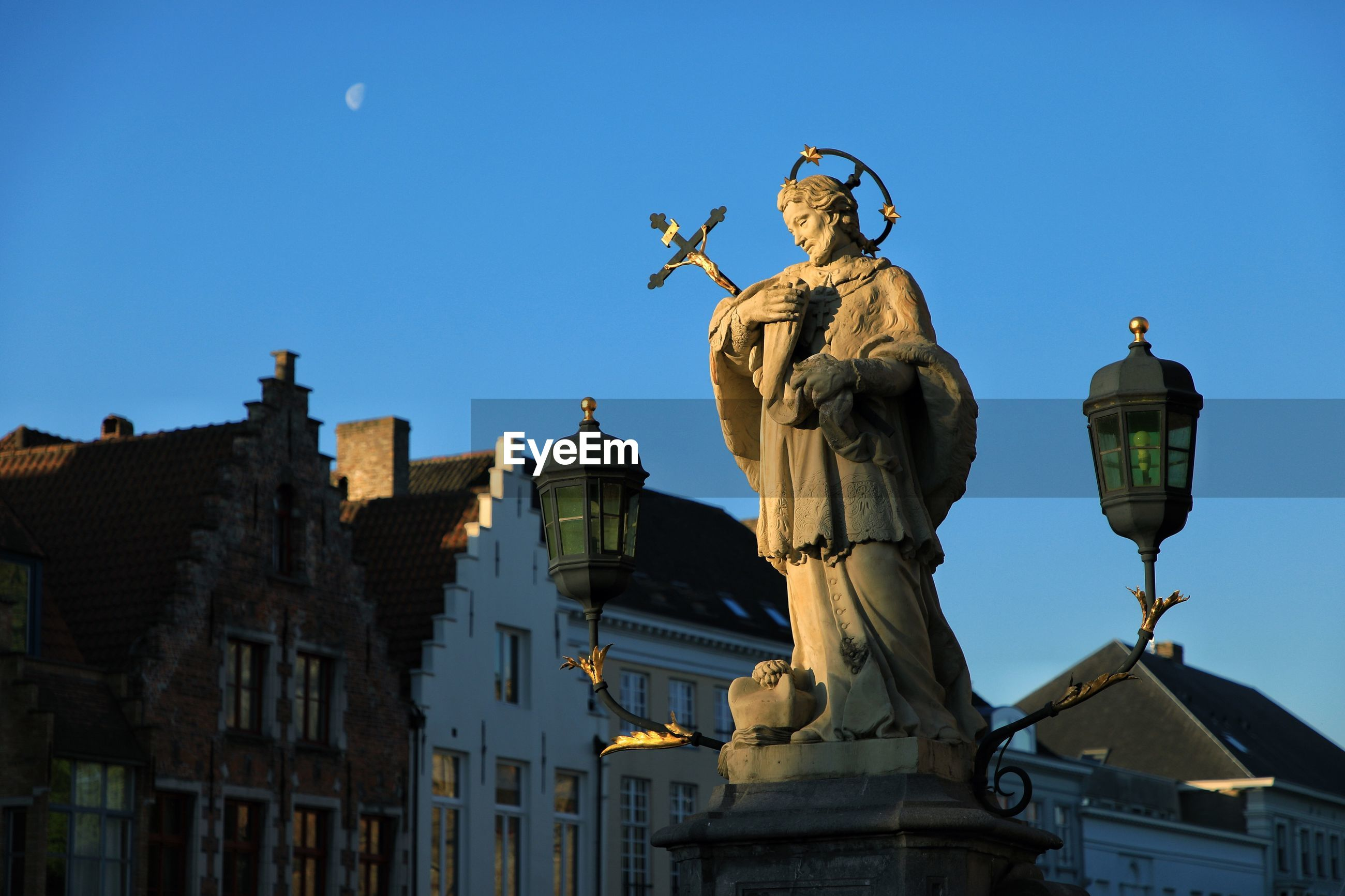 LOW ANGLE VIEW OF ANGEL STATUE AGAINST BUILDINGS
