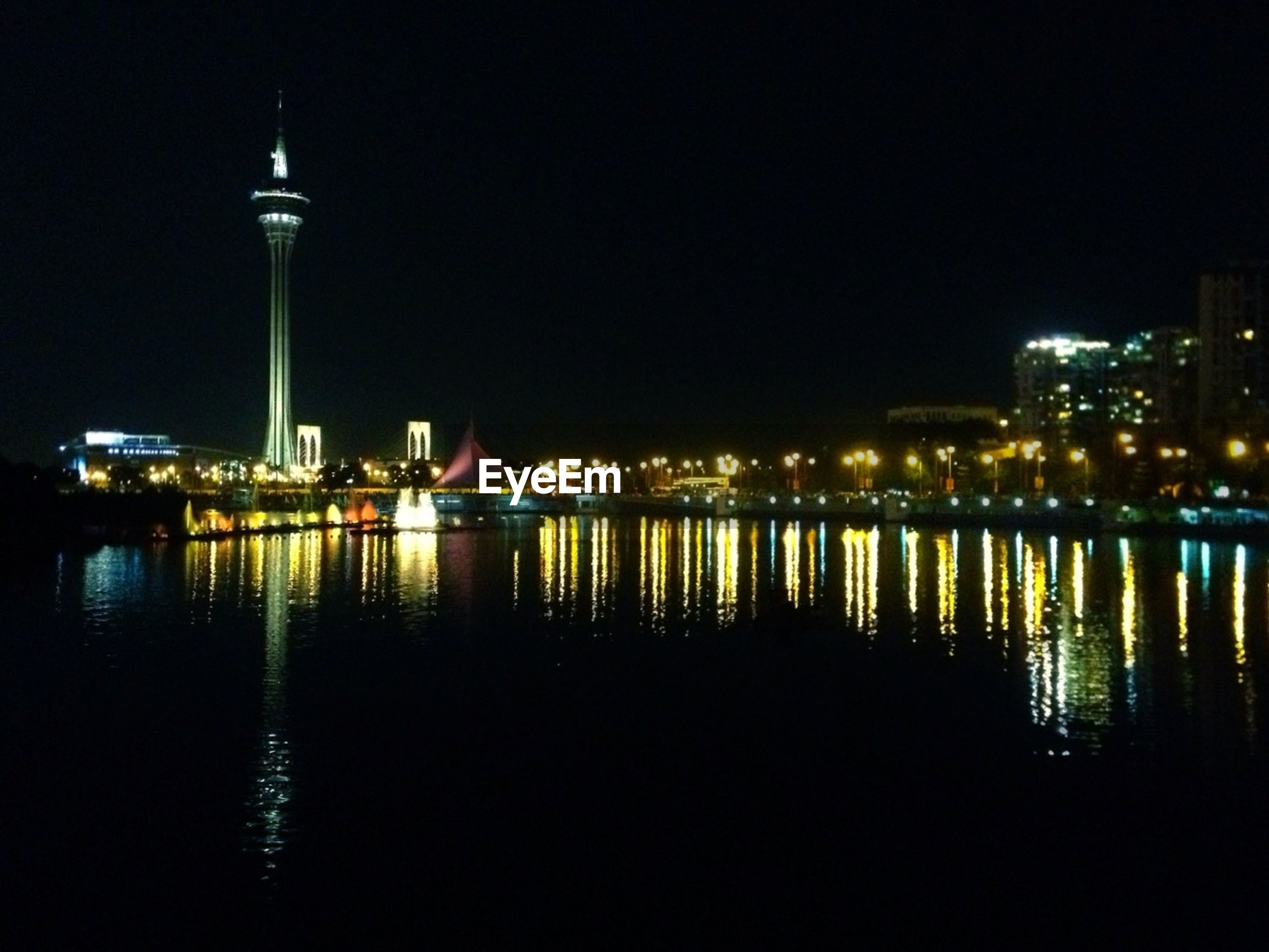 Illuminated macau tower by river against sky at night