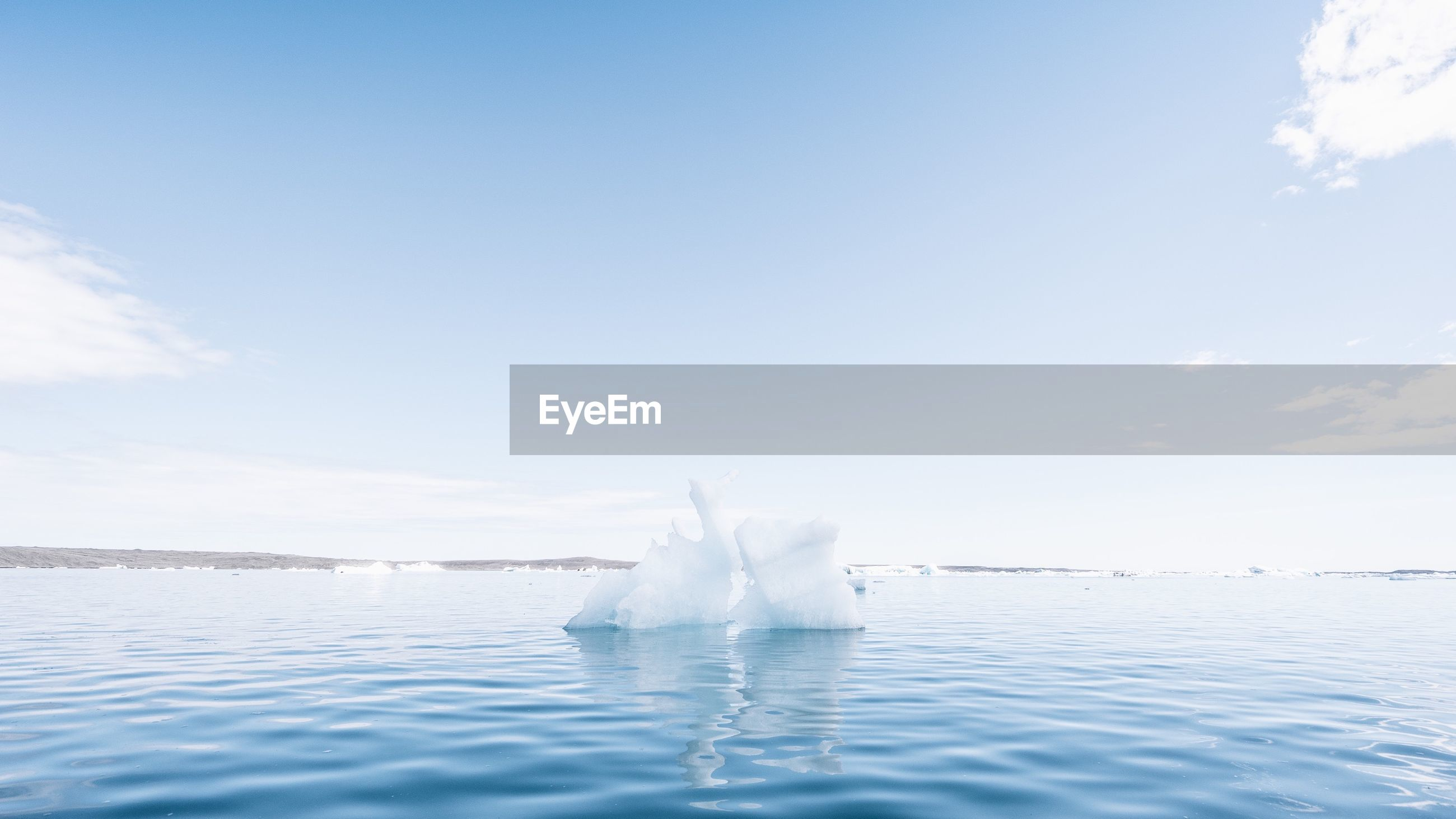 View of iceberg on water surface against sky