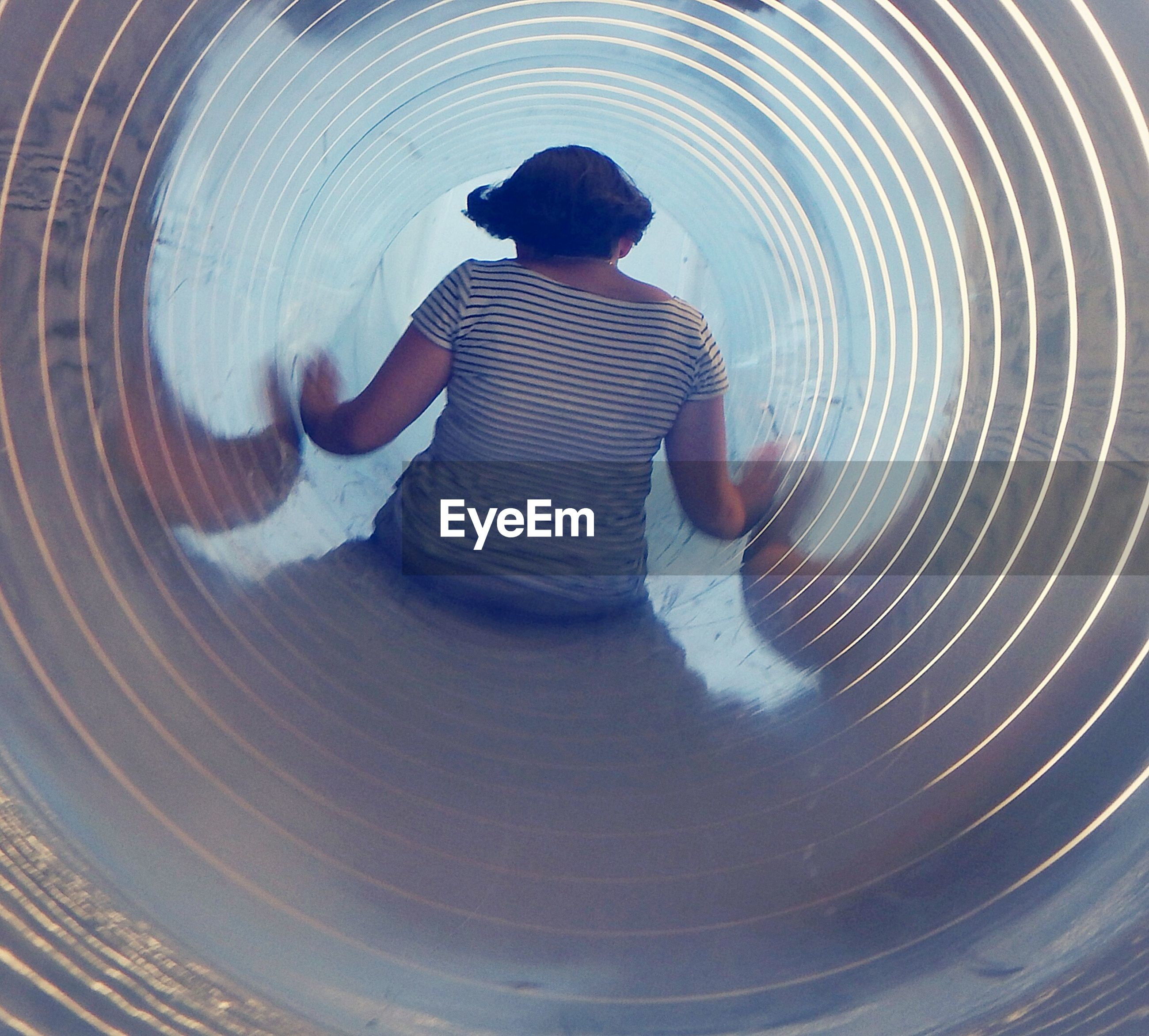 Rear view of woman in slide