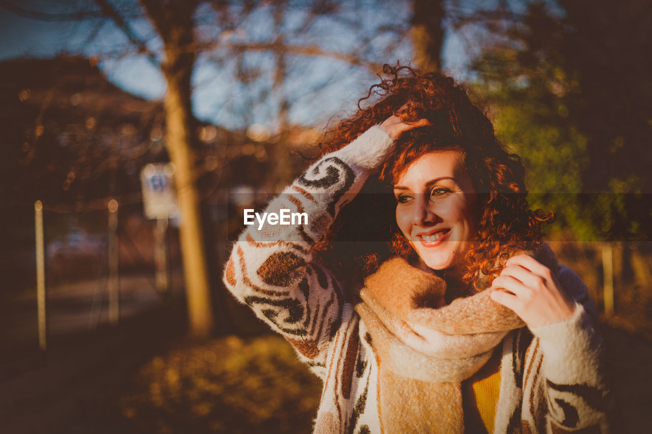 Smiling Young Woman Standing Against Trees During Sunny Day